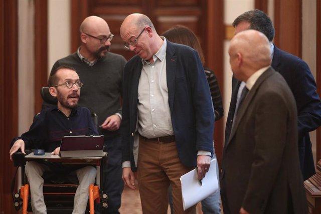 El portavoz de Unidas Podemos en el Congreso, Pablo Echenique (izq) habla con el diputado del PSOE en el Congreso, José Zaragoza (3i), a la salida de la Junta de Portavoces del Congreso de los Diputados, en Madrid (España), a 15 de enero de 2020.