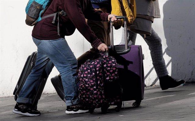 Un grupo de turistas caminan con sus maletas por una calle de Madrid.