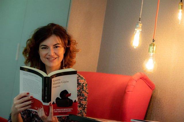 La escritora Susana Martín Gijón posa con su novela 'Progenie', tras una entrevista para Europa Press en la sede de Random House en Madrid (España).