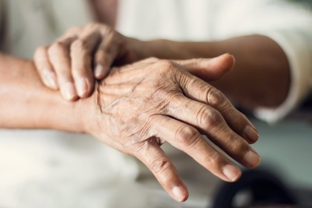 Close up hands of senior elderly woman patient suffering from pakinson's desease symptom. Mental health and elderly care concept
