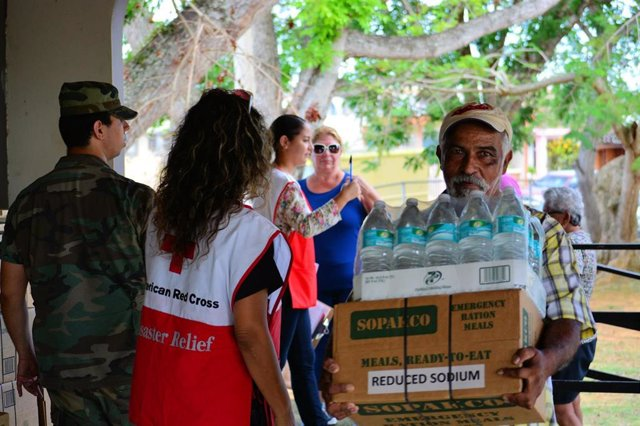 Un hombre recibe ayuda humanitaria por parte de la Cruz Roja tras el paso del huracán María por Puerto Rico en 2017.