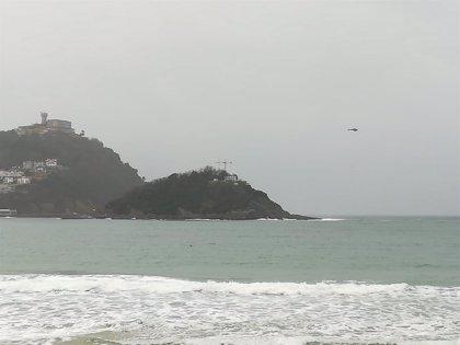 Un helicóptero traslada material de la casa del faro desde la isla al Paseo Nuevo de San Sebastián