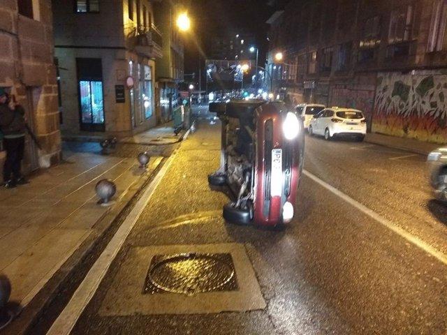 Coche volcado en la calle Falperra de Vigo, cuyo conductor dio positivo en alcoholemia y fue denunciado por un supuesto delito contra la seguridad vial.