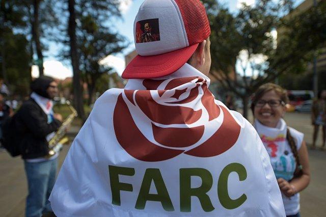 Joven con una bandera del partido político surgido de las FARC