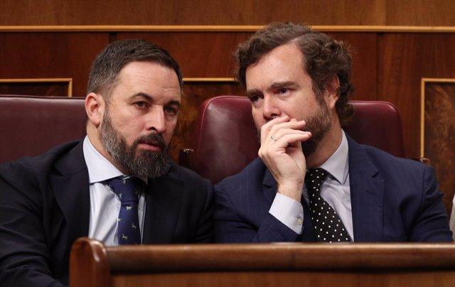 El presidente de Vox, Santiago Abascal, y el portavoz del partido en el Congreso de los Diputados, Iván Espinosa de los Monteros, hablan en sus escaños en el hemiciclo del Congreso