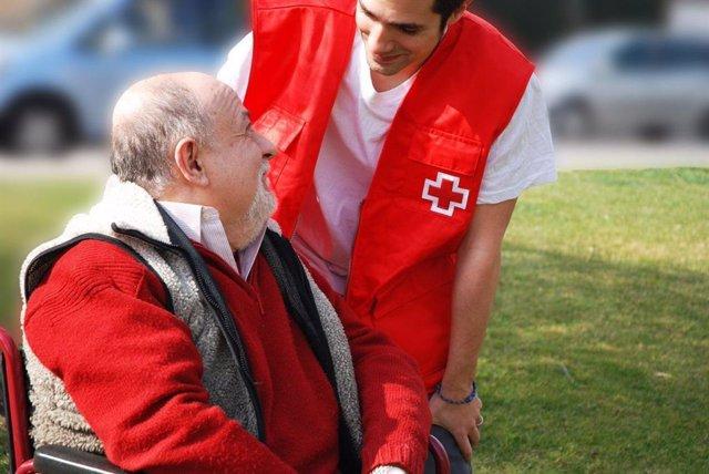 Un voluntario de Cruz Roja atiende a un hombre mayor