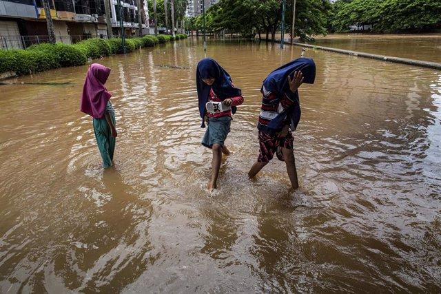 Tres niñas caminan sobre las calles inundadas de Yakarta tras las precipitaciones que cayeron sobre la capital de Indonesia a principios de enero de 2020.