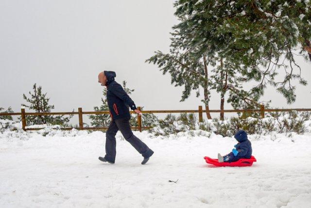 Un padre tira del trineo de su hijo durante el temporal de nieve en la Sierra de Madrid, en el Puerto de Navacerrada (Madrid) a 16 de noviembre de 2019.