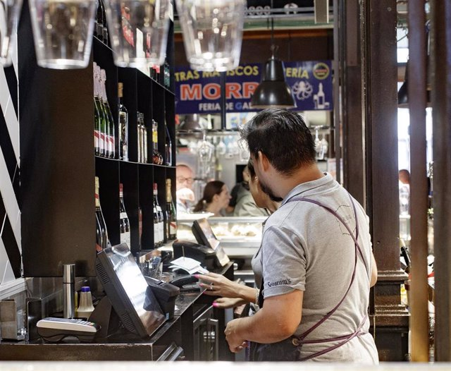 Dos camareros cobran las cuentas de los clientes en un bar de Madrid.