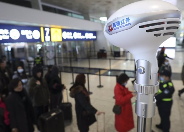 Personal del Aeropuerto Internacional de Tianhe en Wuhan (China) toma la temperatura a pasajeros.
