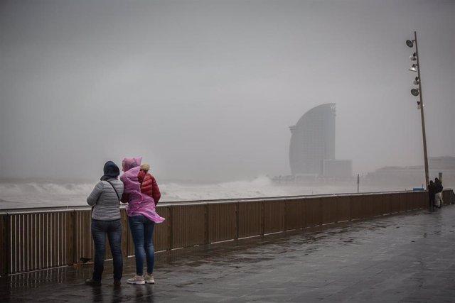 Dos mujeres en el paseo marítimo de Barcelona, donde la borrasca 'Gloria' ha dejado fuertes rachas de viento y lluvia, a 21 de enero de 2020.