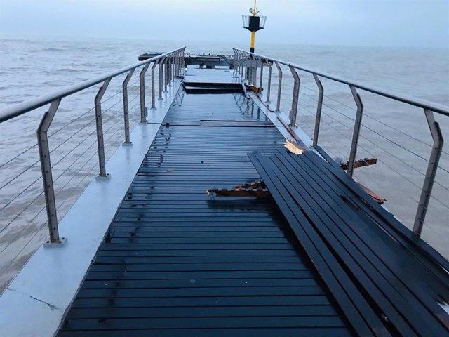 Cau al mar un tram del Pont del Petroli de Badalona (Barcelona) per l'onatge