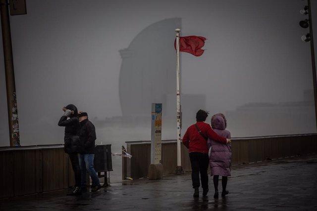 Diverses persones passegen al costat de la bandera vermella de la platja al passeig marítim de Barcelona, on la borrasca Gloria ha deixat fortes ratxes de vent i pluja, 21 de gener del 2020.