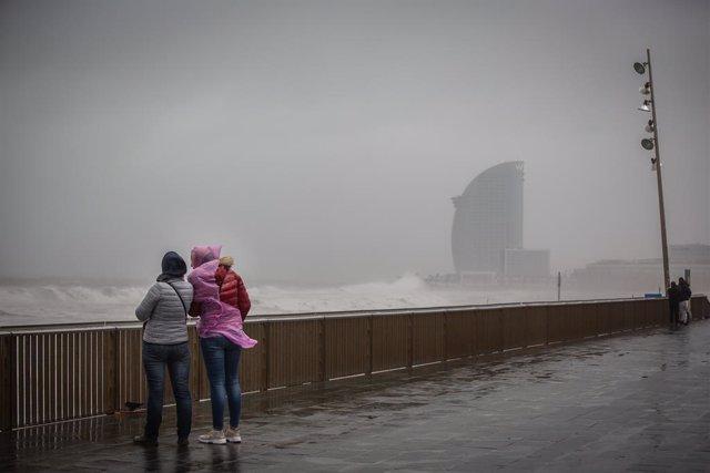 Dues dones al passeig marítim de Barcelona, on la borrasca Gloria ha deixat fortes ratxes de vent i pluja, a 21 de gener del 2020.