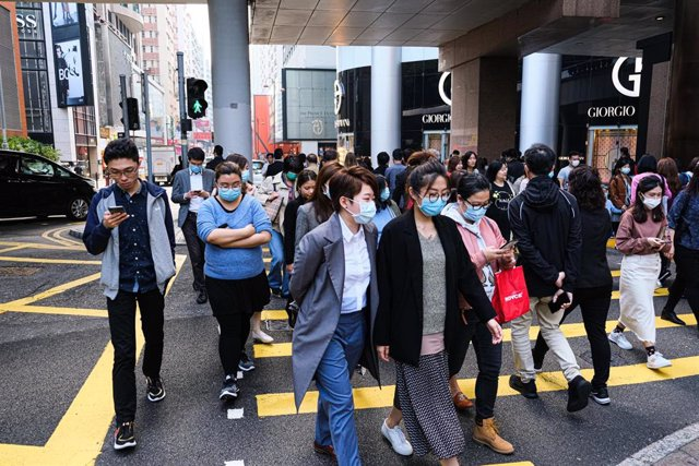 23 January 2020, China, Hong Hong: Locals wear surgical mask and cross the street during lunch hour. Hong Kong is in high alert as the coronavirus outbreak killed 17 people in China so far, travellers are being cautious and many put on surgical mask as
