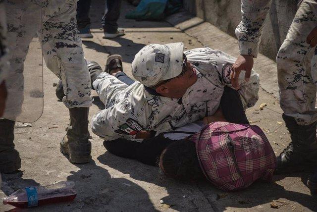 Un agente de la Guardia Nacional de México detiene a un migrante centroamericano en la frontera con Guatemala.