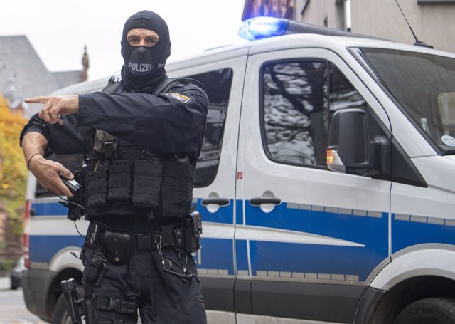 13 November 2019, Frankfurt/Main: Masked officers of a special police unit secure the evacuation of a suspected terrorist man who had previously been brought before the magistrate at the court centre. Photo: Boris Roessler/dpa