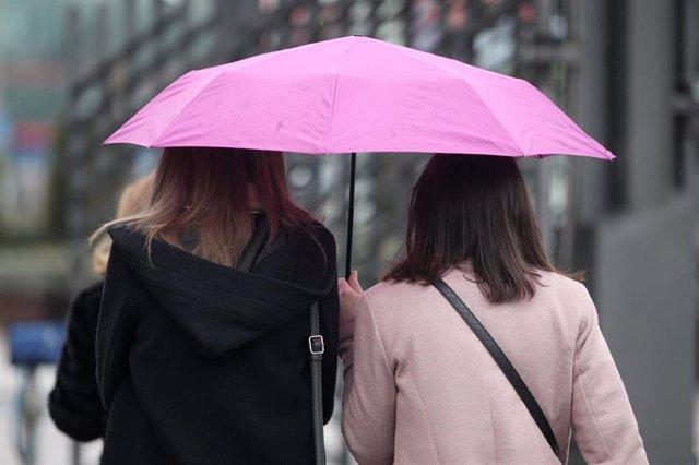 Dos mujeres pasean con paraguas para protegerse de la lluvia