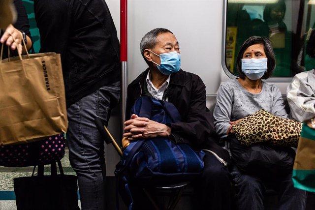 Imagen de pasajeros en China con una mascarilla.