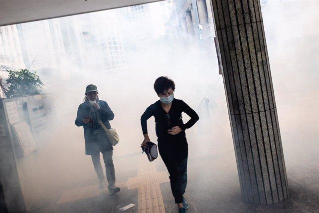 Personas corriendo en medio de gases lacrimógenos durante una protesta en Hong Kong.