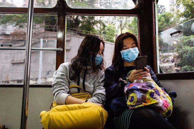 Dos mujeres en el transporte público de Hong Kong usando las mascarillas que el Gobierno de China ha recomendado utilizar debido a la rápida propagación dle coronavirus.