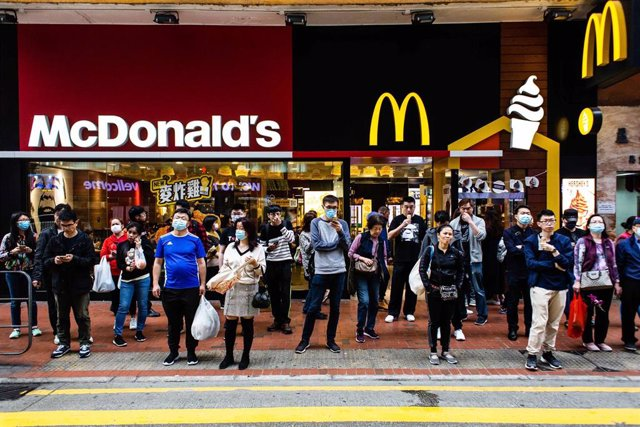24 January 2020, China, Hong Kong: People wearing surgical masks stand in front of a McDonald's branch amid the outbreak of the coronavirus. Photo: Willie Siau/SOPA Images via ZUMA Wire/dpa
