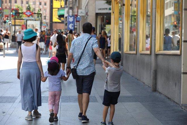Una familia pasea de la mano por una calle de Madrid.