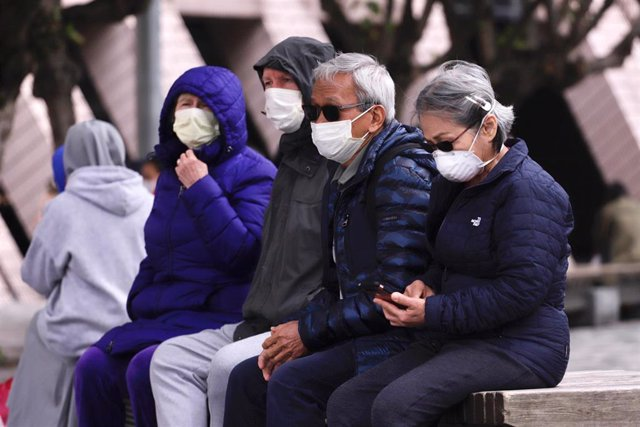 27 January 2020, China, Hong Kong: People rest on the bench while wearing surgical masks amid the outbreak of the coronavirus. Photo: Liau Chung Ren/ZUMA Wire/dpa