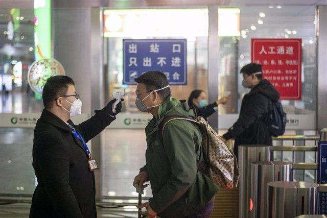 Personal de una estación de tren en China toma la temperatura a un viajero.