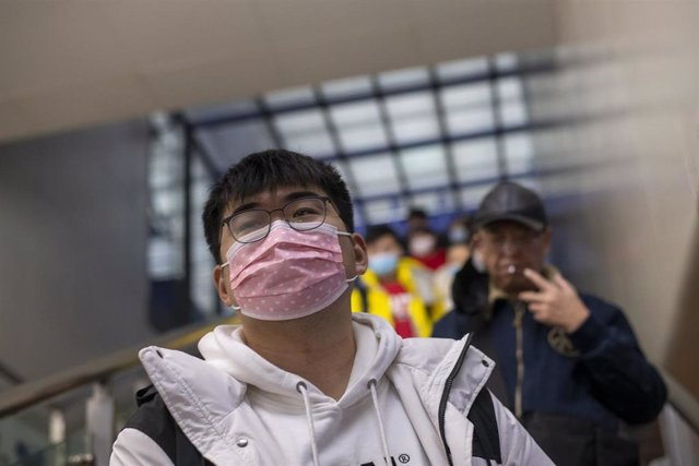 January 27, 2019 - Shanghai, China: A young man wears face masks in wake of the coronavirus outbreak as he rides an escalator to the platform from which a high speed train to Nanning, Guangxi Province, will depart. Hongqiao Railway Station was unusually q