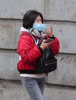 Una asiática pasea por la calle con una mascarilla. La Organización Mundial de la Salud, (OMS) ha elevado este lunes a 'Alta' la amenaza internacional por el Coranavirus de Wuhan, en Madrid (España), a 28 de enero de 2020.