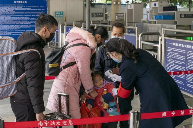 Nanning, China - A child shows relecutance to be tested for fever by security staff at Nanning Railway Station wear in wake of the coronavirus outbreak,