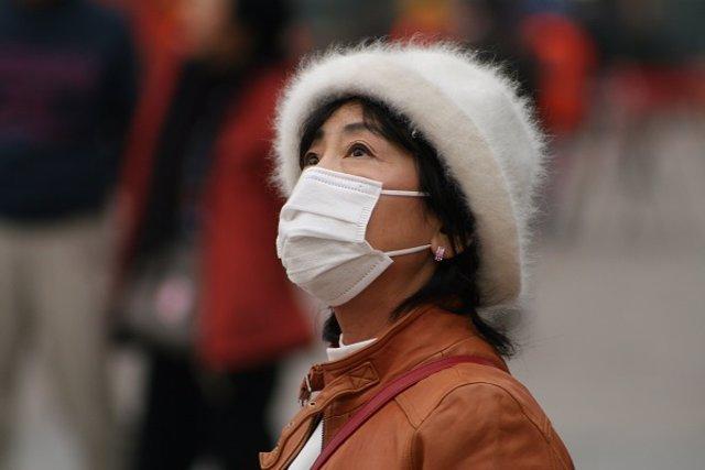Una mujer con una mascarilla para evitar contagiarse en China.