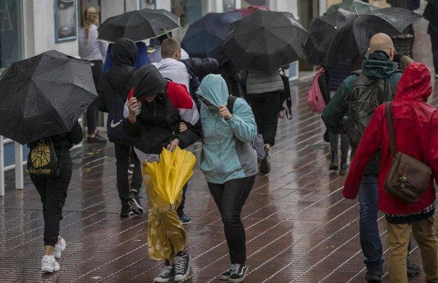 Personas caminando por la calle bajo la lluvia