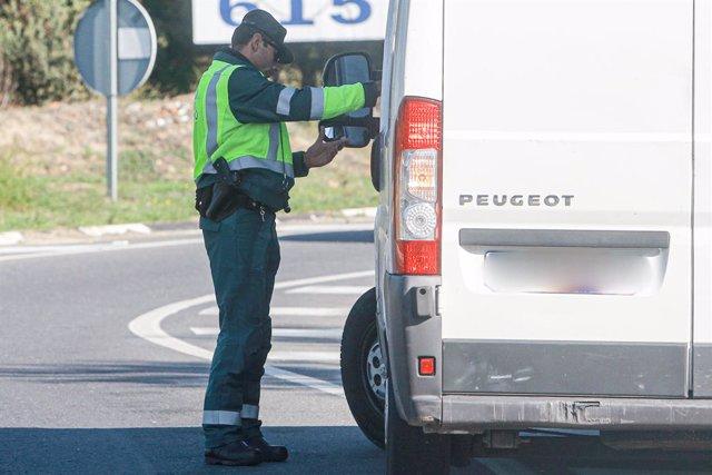 Un agente de la Guardia Civil de Tráfico pide la documentación a una furgoneta