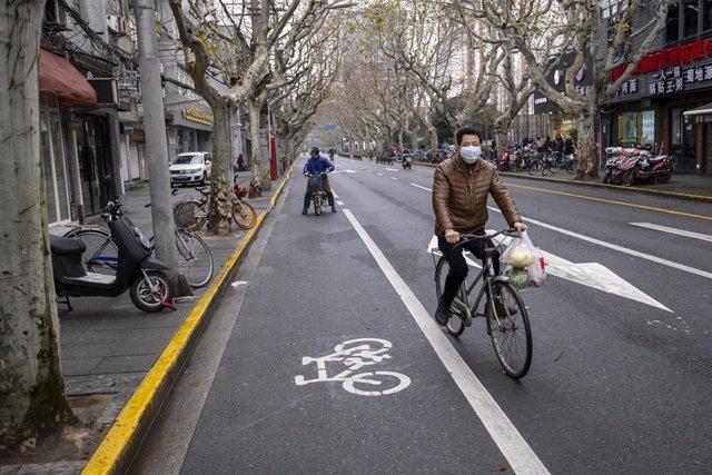 Un ciclista con mascarilla en Shanghai