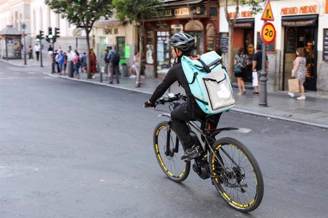 Fotografía de un repartidor de la empresa de reparto Deliveroo transitando en bicliceta por una calle del centro de Madrid.