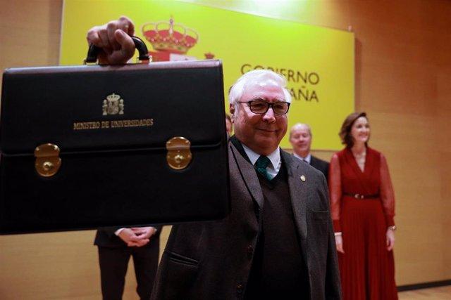 El nuevo ministro de Universidades, Manuel Castells, muestra la cartera de del ministerio de Universidades durante el acto de toma de posesión de los ministros