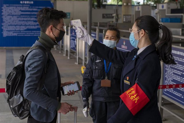 January 28, 2019, Nanning, China - A commuter's temperature is tested by security staff at Nanning Railway Station wear in wake of the coronavirus outbreak, which has five reported cases in this city of more than seven million. The entire city of Wuhan (p