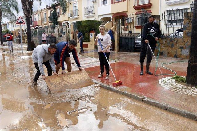Vecinos de Campanillas limpian las calles tras la tormenta.