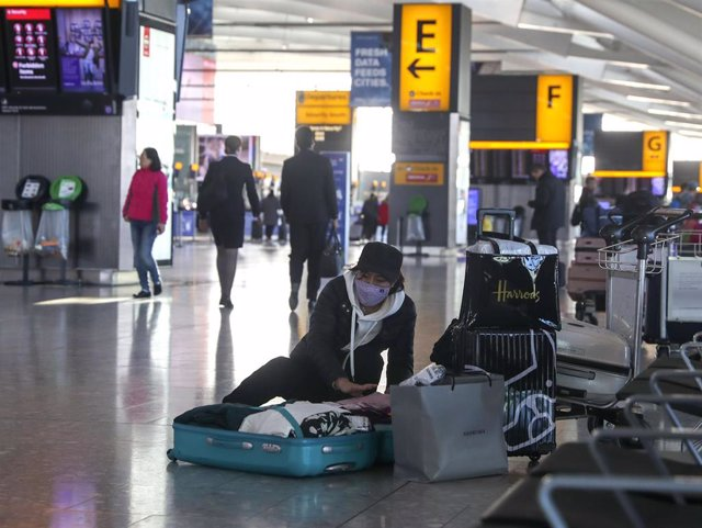 29 January 2020, England, London: A woman wearing a face mask packs her suitcase in the departures area of Terminal 5 at Heathrow Airport, after the British Airways has said that it has suspended all flights to and from mainland China with immediate effec