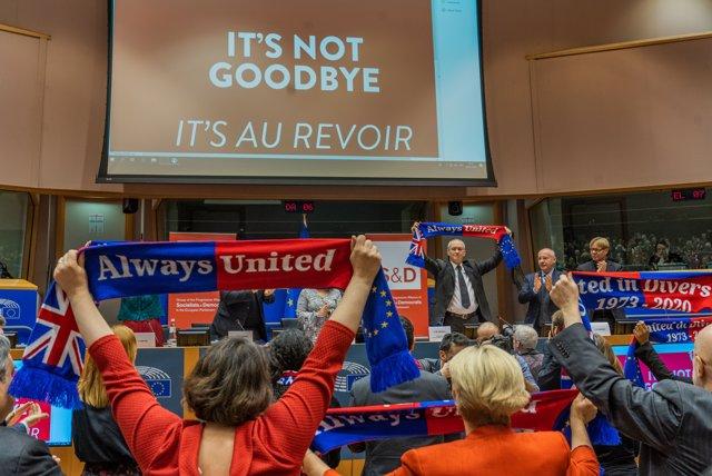 Miembros del Parlamento europeo sostienen bufandas con el lema