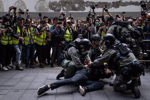 Policías detienen a un manifestante en una protesta por la democracia en Hong Kong