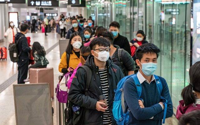 Viajeros con máscaras esperan un taxi tras llegar a la estación de tren de alta velocidad de Hong Kong
