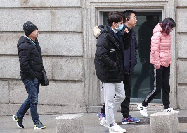 Grupo de asiáticos turistas pasean por la calle y uno de ellos lleva una mascarilla. La Organización Mundial de la Salud  (OMS) ha elevado este lunes a 'Alta' la amenaza internacional por el Coranavirus de Wuhan, en Madrid (España), a 28 de enero de 2020.