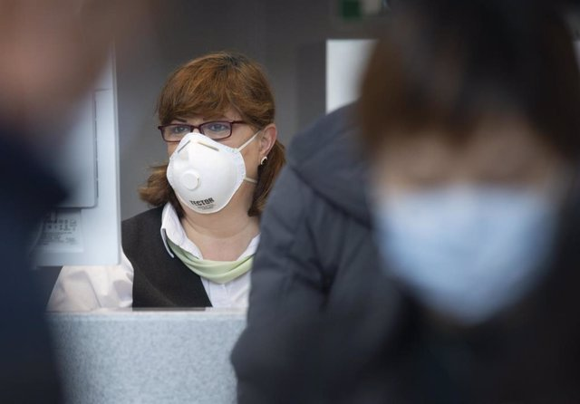 30 January 2020, Frankfurt/Main: A China Southern Airlines employee wears a face masks as passengers wait at Frankfurt Airport for the check-in of the Chinese airline Air China. Photo: Dorothee Barth/dpa