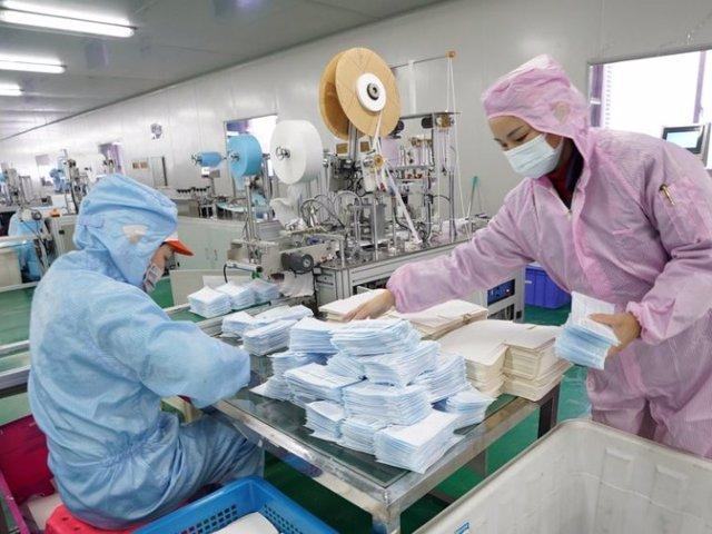 Los trabajadores hacen máscaras faciales en el taller de una empresa en Wuhan, provincia de Hubei, en el centro de China, el 28 de enero de 2020.