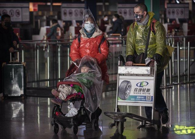 Una familia con máscaras protectoras  en el aeropuerto de Beijing, China.