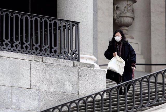 Una mujer asiática pasea con una mascarilla protectora, mientaras las farmacias registran una alta demanda de estas, por parte de ciudadanos chinos tras el coronavirus, en Madrid (España), a 30 de enero.