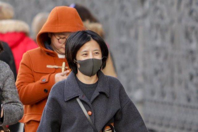 Una mujer asiática pasea con una mascarilla protectora, mientras las farmacias registran una alta demanda de estas por parte de ciudadanos chinos tras el coronavirus, en Madrid (España), a 30 de enero.